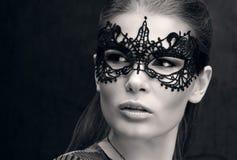 Zwart-wit close-upportret van een mooie jonge vrouw in zwart kantmasker op de ogen stock afbeelding
