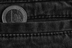 Zwart-wit Euro muntstuk met een benaming van één euro in de zak van blauwe denimjeans Royalty-vrije Stock Afbeeldingen