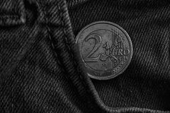 Zwart-wit Euro muntstuk met een benaming van twee euro in de zak van oude uitstekende blauwe denimjeans Stock Fotografie