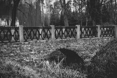 Zwart-wit mening van oude steenbrug over rivier bij park Royalty-vrije Stock Afbeelding
