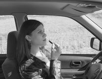 Zwart-wit, mooi meisje in de auto die op lippenstift zetten Stock Foto