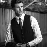 Zwart-wit openluchtportret van de elegante knappe mens in klassiek vest dichtbij houten omheining stock afbeelding