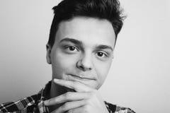 Zwart-wit portret van een glimlachende tiener De leuke kerel onderzoekt de camera, hand die zijn kin wrijven Royalty-vrije Stock Fotografie