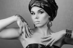 Zwart-wit portret van een mooi meisje in een tulband en mehendipatroon op een hand Stock Foto