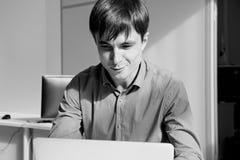 Zwart-wit portret van een smilling mens voor een laptop computer in bureau royalty-vrije stock fotografie