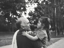 Zwart-wit portret van Gelukkige grootvader en grandaughter het spelen bij het park royalty-vrije stock foto