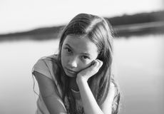 Zwart-wit portret van het Droevige Mooie tienermeisje bekijken met ernstig gezicht kust tijdens zonsondergang stock fotografie