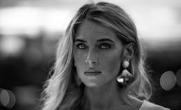 Zwart-wit Portret van mooi jong blonde in het turkooise overhemd op de achtergrond van de lichten van de nachtstad modern stock foto