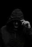 Zwart-wit Silhouet van een mens met een kap, op zwarte royalty-vrije stock afbeeldingen
