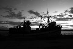 Zwart-wit silhouet van vissersboot stock foto's