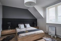 Zwart-wit slaapkamer met grijze muren en lampen Stock Fotografie