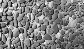 Zwart-wit textuur als achtergrond vele kiezelstenen in een concrete muur royalty-vrije stock fotografie