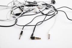 Zwart-wit verwarde kleine hoofdtelefoons liggen op een wit geïsoleerde achtergrond Horizontaal kader Stock Fotografie