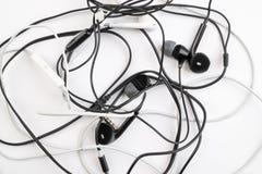 Zwart-wit verwarde kleine hoofdtelefoons liggen op een wit geïsoleerde achtergrond Horizontaal kader Stock Afbeeldingen