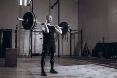 Zwart-wit volledig lengteportret van de Sterke mens die een barbell opheffen tijdens crossfittraining bij gymnastiek Royalty-vrije Stock Afbeeldingen