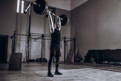 Zwart-wit volledig lengteportret van de Sterke mens die een barbell opheffen tijdens crossfittraining bij gymnastiek Royalty-vrije Stock Fotografie