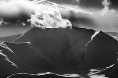 Zwart-witte bergen in zonsondergang met zonovergoten wolken Stock Foto