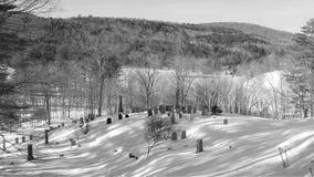 Zwart-witte de winterbegraafplaats in vroege ochtendzon royalty-vrije stock foto