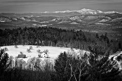 Zwart-witte de winterscène met sneeuwgebieden en bergen stock fotografie