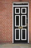 Zwart-witte deur met een bakstenen muur Stock Foto