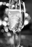 Zwart-witte die foto van champagne in glazen wordt gegoten Stock Afbeeldingen