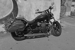 Zwart-witte die motorfiets tegen de muur in de yard wordt geparkeerd stock foto's