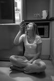 Zwart-witte foto van hongerige vrouw die pizza op keukenfl eten Royalty-vrije Stock Fotografie