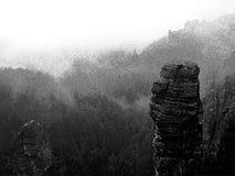 Zwart-witte gestormde retro schets De herfst vroege ochtend, dalingsvallei Zandsteenpieken en heuvels van zware mist worden verho Stock Afbeeldingen