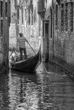 Zwart-witte gondelier en zijn gondel, Venetië, Italië royalty-vrije stock afbeeldingen
