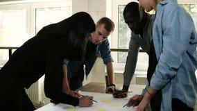 Zwart-witte groep die mensen een project in bureau samen bespreken Planningsstappen die met gele stickers richten stock videobeelden