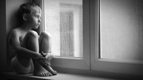 Zwart-witte lengte van een droevige jongenszitting op de vensterbank tijdens stortbui, onbekwaam om uit de flat te krijgen