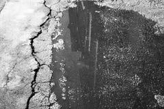 Zwart-witte noirachtergrond met bezinning van het gebouw in een vulklei en barst in het asfalt royalty-vrije stock foto's