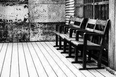 Zwart-witte oude houten stoel in de oude houten de muurwijnoogst van het ruimte Oude ijzer Royalty-vrije Stock Fotografie