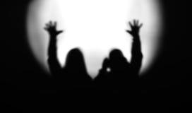 Zwart-witte paarsilhouetten met handen omhoog gezien flo Stock Fotografie