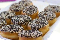 Zwart-witte sesamzaaddoughnuts op bakkerijdienblad Stock Fotografie