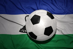 Zwart-witte voetbalbal op de nationale vlag van Lesotho Royalty-vrije Stock Fotografie