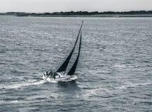 Zwart-witte zeilboot die stormachtige wateren navigeren Stock Afbeeldingen