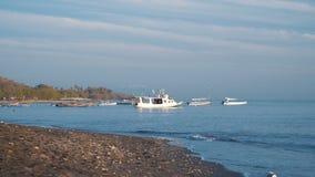 Zwart zandstrand en kleine witte boten in overzees stock videobeelden
