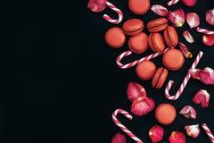 Zwarte achtergrond met bloemblaadjes van rode rozen, makarons en karamelstokken Stock Foto