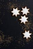 Zwarte achtergrond met een peperkoek in de vorm van sterren Stock Afbeeldingen