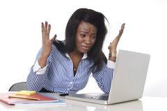 Zwarte Afrikaanse Amerikaanse het behoren tot een bepaald ras gefrustreerde vrouw die in spanning op kantoor werken Stock Foto