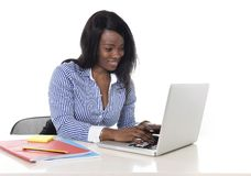 Zwarte Afrikaanse Amerikaanse het behoren tot een bepaald rasvrouw die bij computerlaptop bij bureau gelukkig glimlachen werkt Stock Foto's