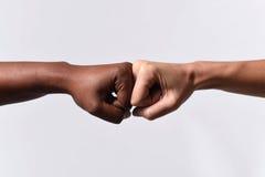 Zwarte Afrikaanse Amerikaanse ras vrouwelijke hand wat betreft gewrichten met witte Kaukasische vrouw in multiraciale diversiteit Stock Foto's