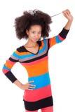 Zwarte Afrikaanse Amerikaanse tiener die haar afrohaar houden Stock Fotografie