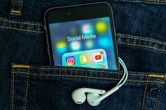 Zwarte Apple-iPhone met pictogrammen van sociale media toepassing op het scherm met de achtergrond van denimjeans royalty-vrije stock afbeelding