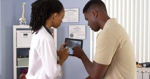 Zwarte arts die tabletcomputer met behulp van om röntgenstraal met patiënt te delen Stock Foto's