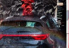 Zwarte auto in automatische autowasserette stock afbeeldingen