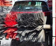 Zwarte auto in automatische autowasserette stock foto's