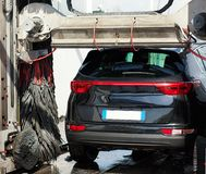 Zwarte auto in automatische autowasserette royalty-vrije stock afbeeldingen