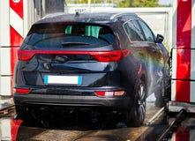 Zwarte auto in automatische autowasserette stock fotografie